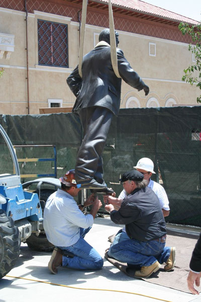 Sculptor Lawrence Noble supervises the installation of the bronze  at USC