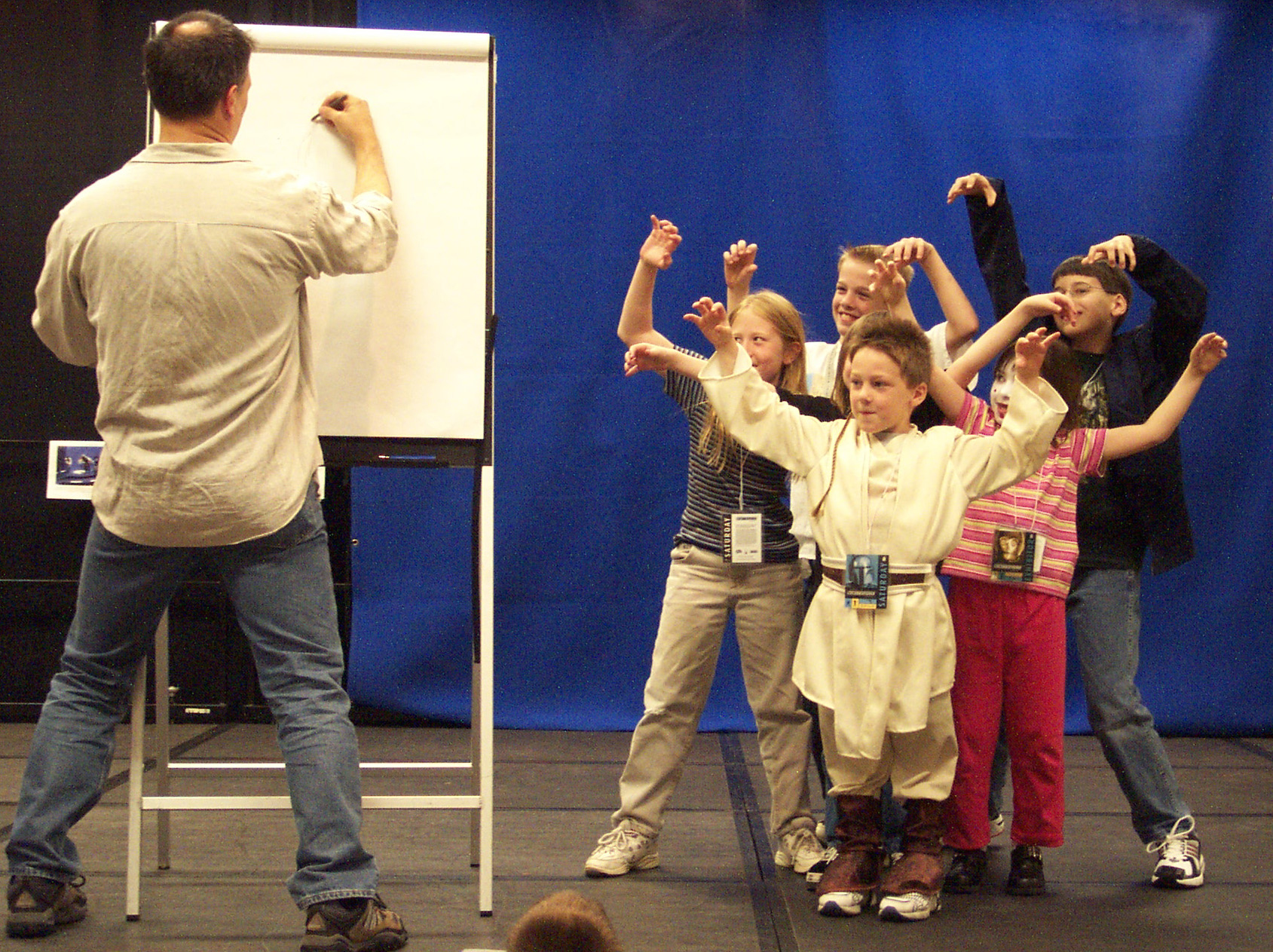 "Iain McCaig, concept artist for the Star Wars prequels, led eager kids in his class, ""A Day in the Star Wars Art Department."" McCaig taught young artists how to draw Star Wars creatures in the Star Wars Family Room during Celebration II. The Family Room featured drawing classes, face painting, letters to Yoda, craft projects, costume contests, and a stage for acting out favorite scenes from the films. Since Celebration II, the Star Wars Family Room has grown in programming scope and size. It's an essential part of all Celebrations. Photo by Dennis VonGalle."
