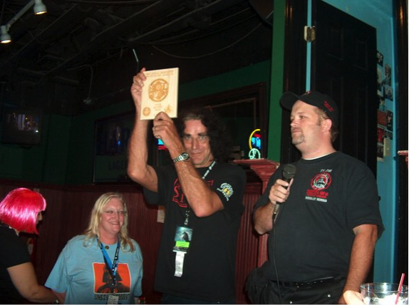 Peter Mayhew holds up one of the Droid Hunt awards at the 501st Mixer