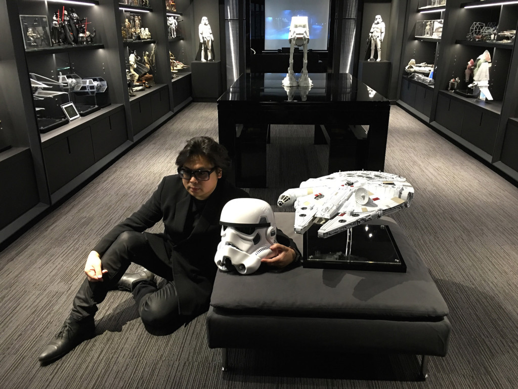 Barrie Ho sitting with a stormtrooper helmet and Millennium Falcon