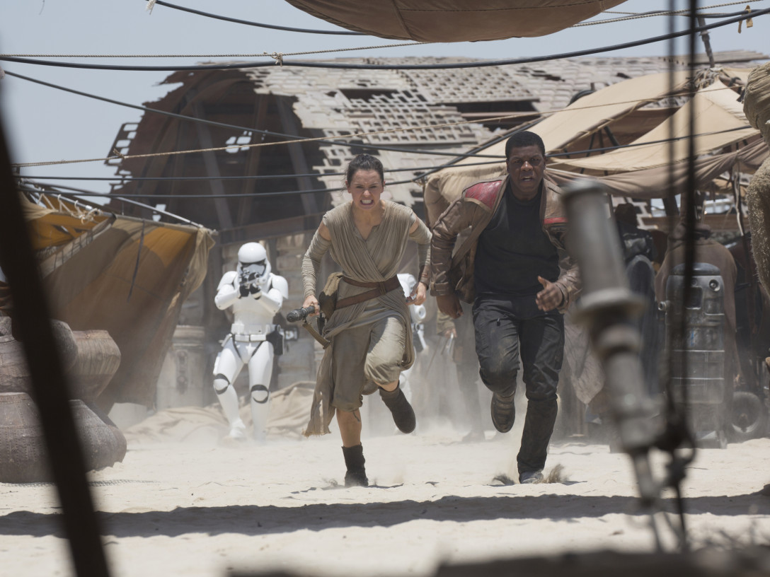 Rey and Finn fleeing from First Order Stormtroopers on Jakku