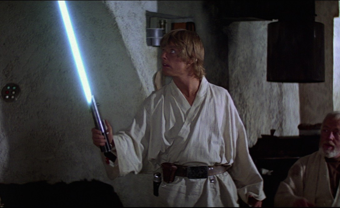 Luke Skywalker igniting his father's lightsaber for the first time