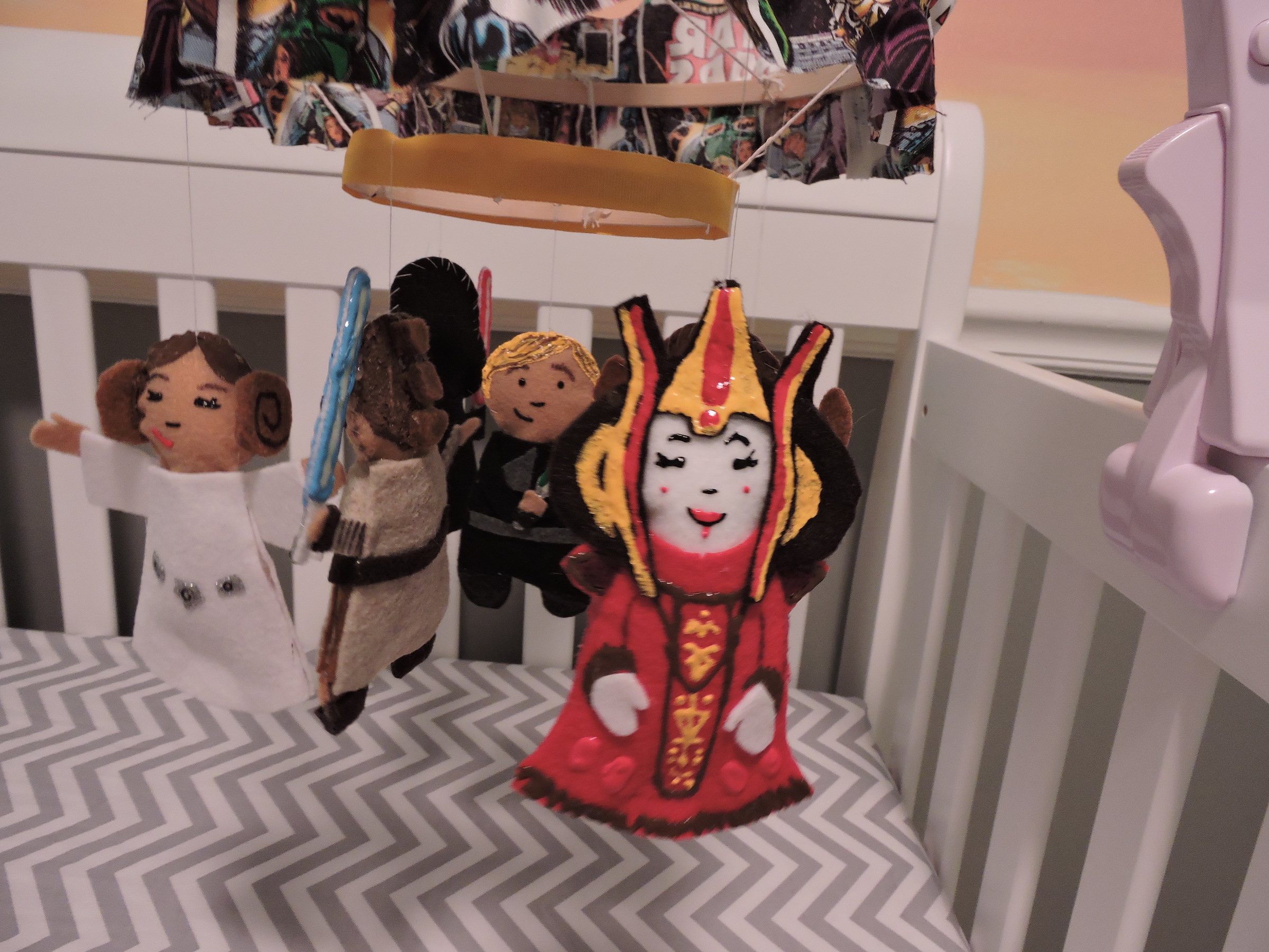 Crib mobile with toys depicting various Star Wars characters