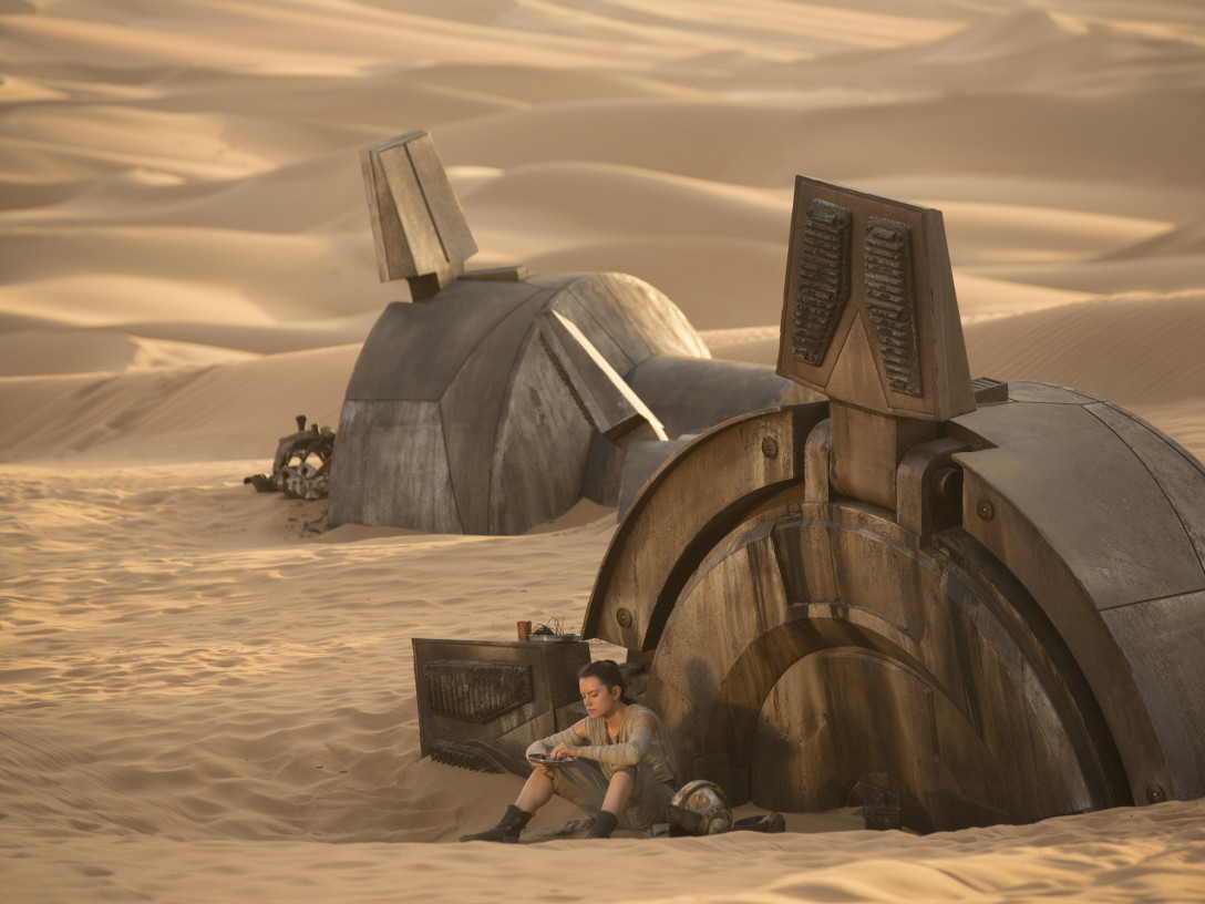 Rey eating a meal beside the remains of a derelict AT-AT