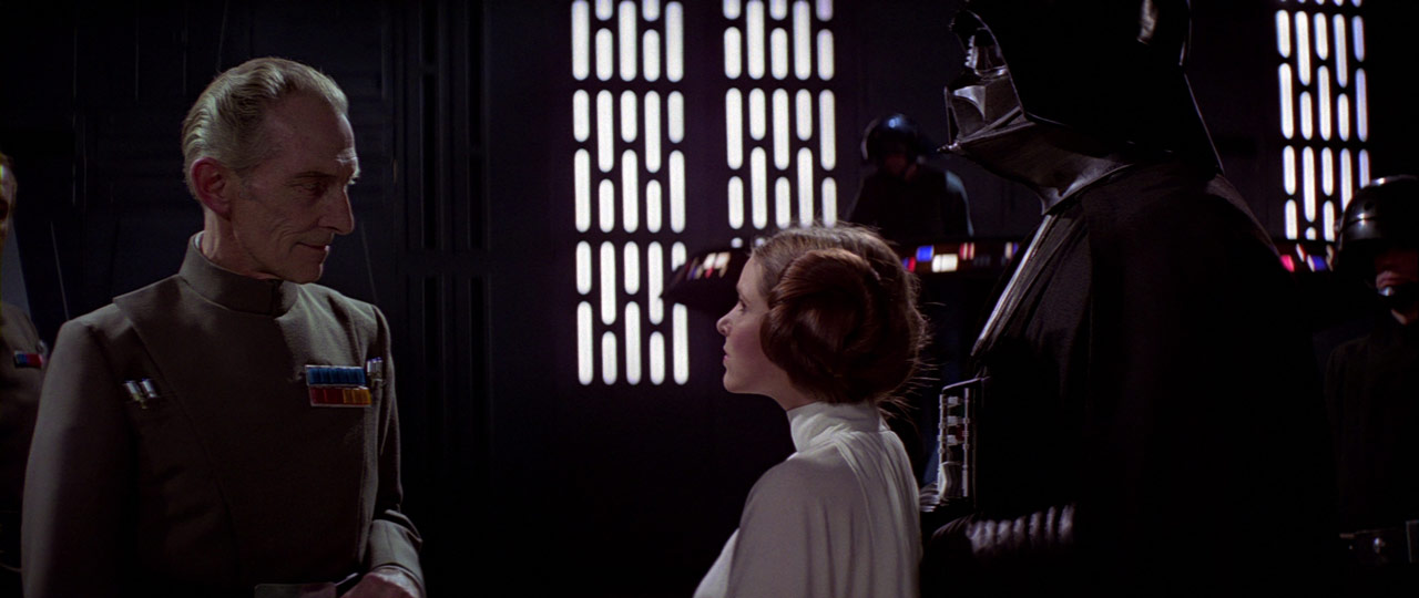 Governor Tarkin speaks to Darth Vader and Princess Leia.