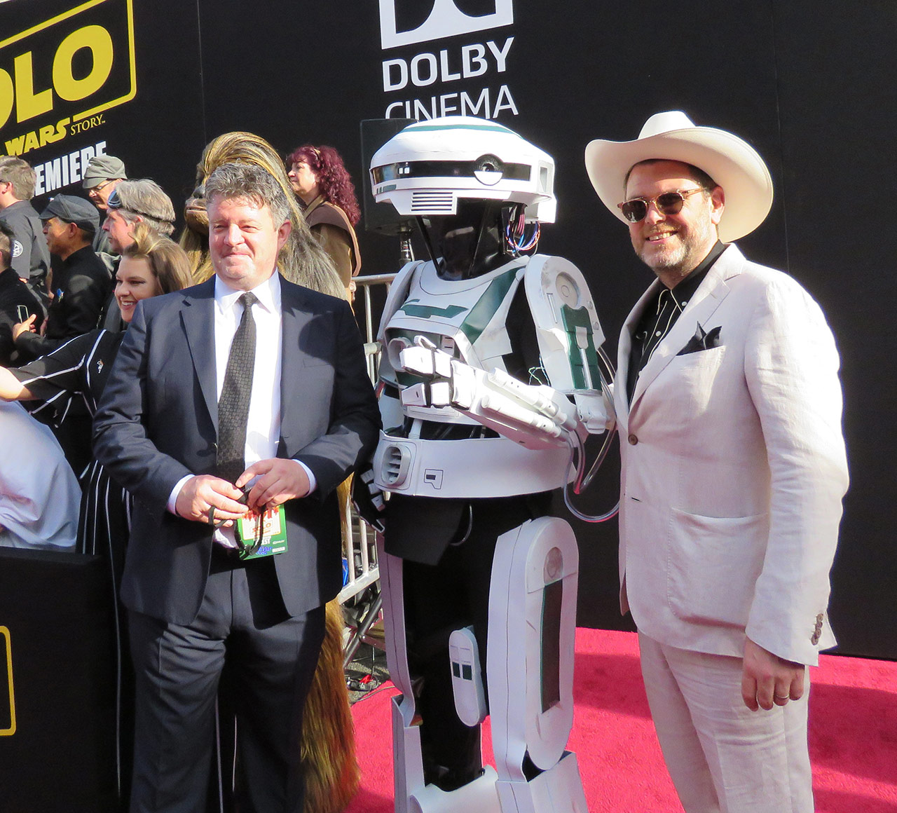 Costume designers David Crossman, left, and Glyn Dillon, right, stop to pose with cosplayer Darren Moser, dressed as L3-37, during the world premiere of <em>Solo: A Star Wars Story</em>.