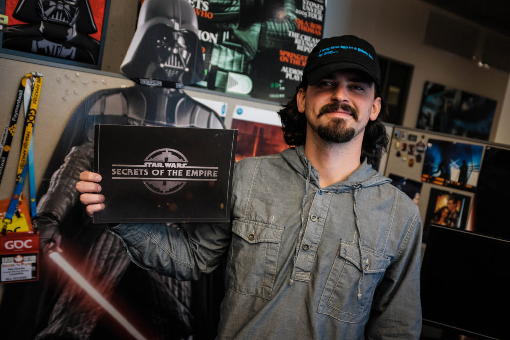 A member of the Lucasfilm Games Team holds up artwork for Star Wars: Secrets of the Empire.