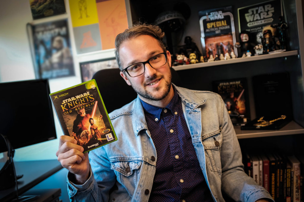 A member of the Lucasfilm Games Team holds up a copy of Knights of the Old Republic.