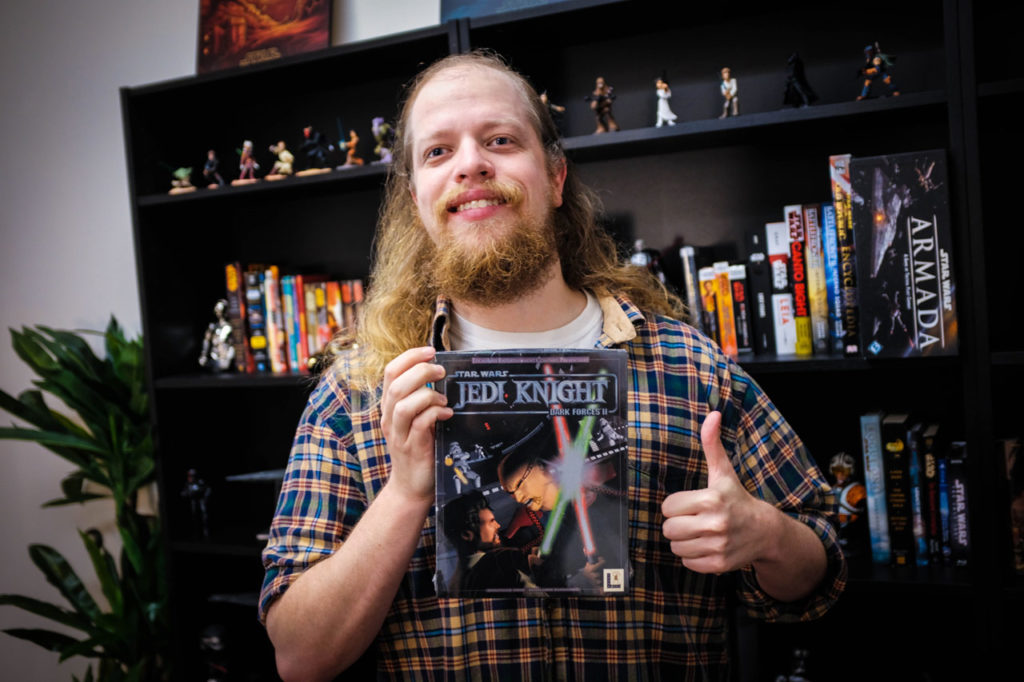 A member of the Lucasfilm Games Team holds up a copy of Dark Forces II: Jedi Knight.