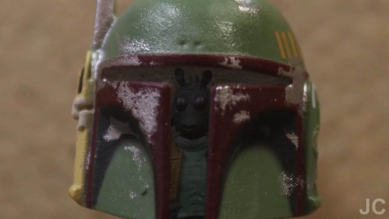 "Greedo is reflected in Boba Fett's helmet in a scene from ""Bounty Buddies."""