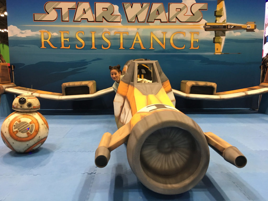 Bria LaVorgna in the Fireball cockpit at NYCC with BB-8.
