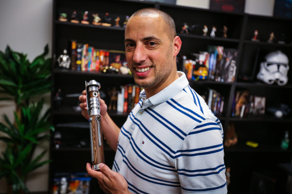 Lucasfilm's Marco Crescenti holding a lightsaber gifted to the Star Wars: The Old Republic games team.