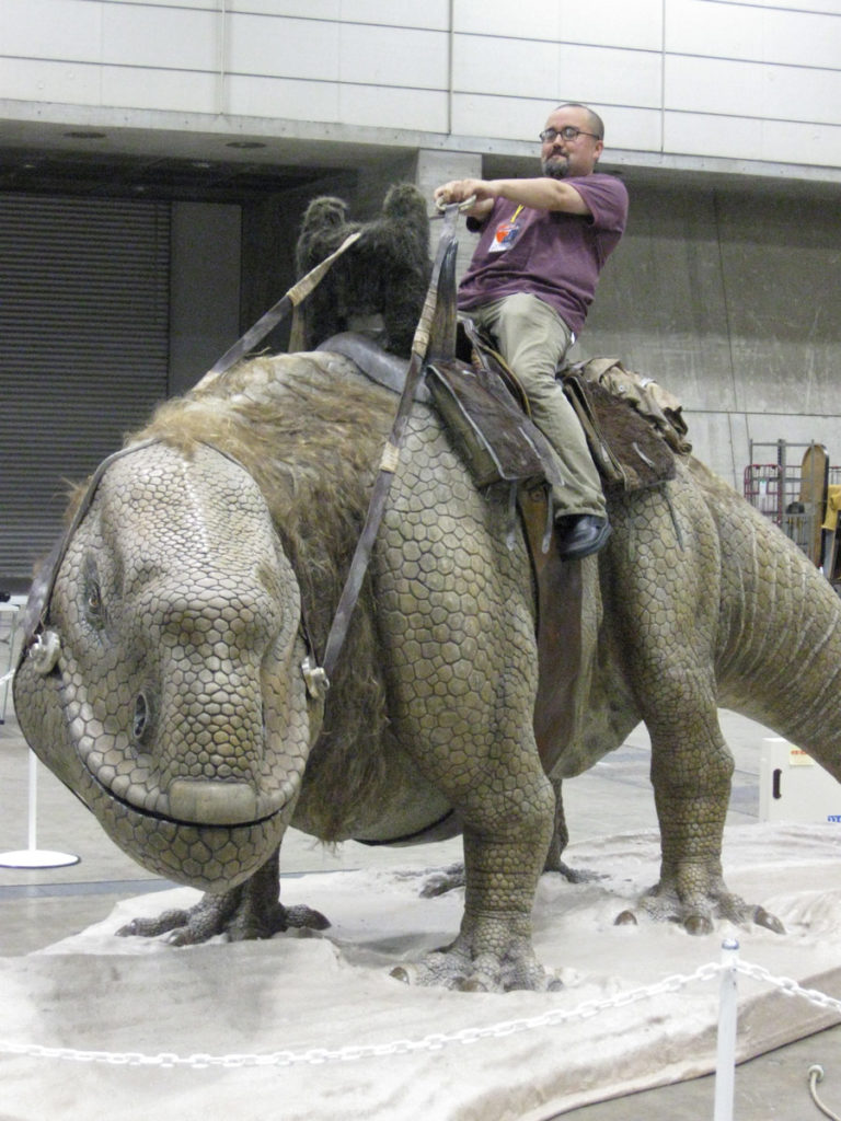 Pablo Hidalgo of Lucasfilm rides a dewback fan-made prop at Star Wars Celebration.