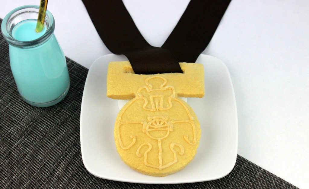 A top-down shot of a plated Medallion of Yavin cookie and a jar of blue milk
