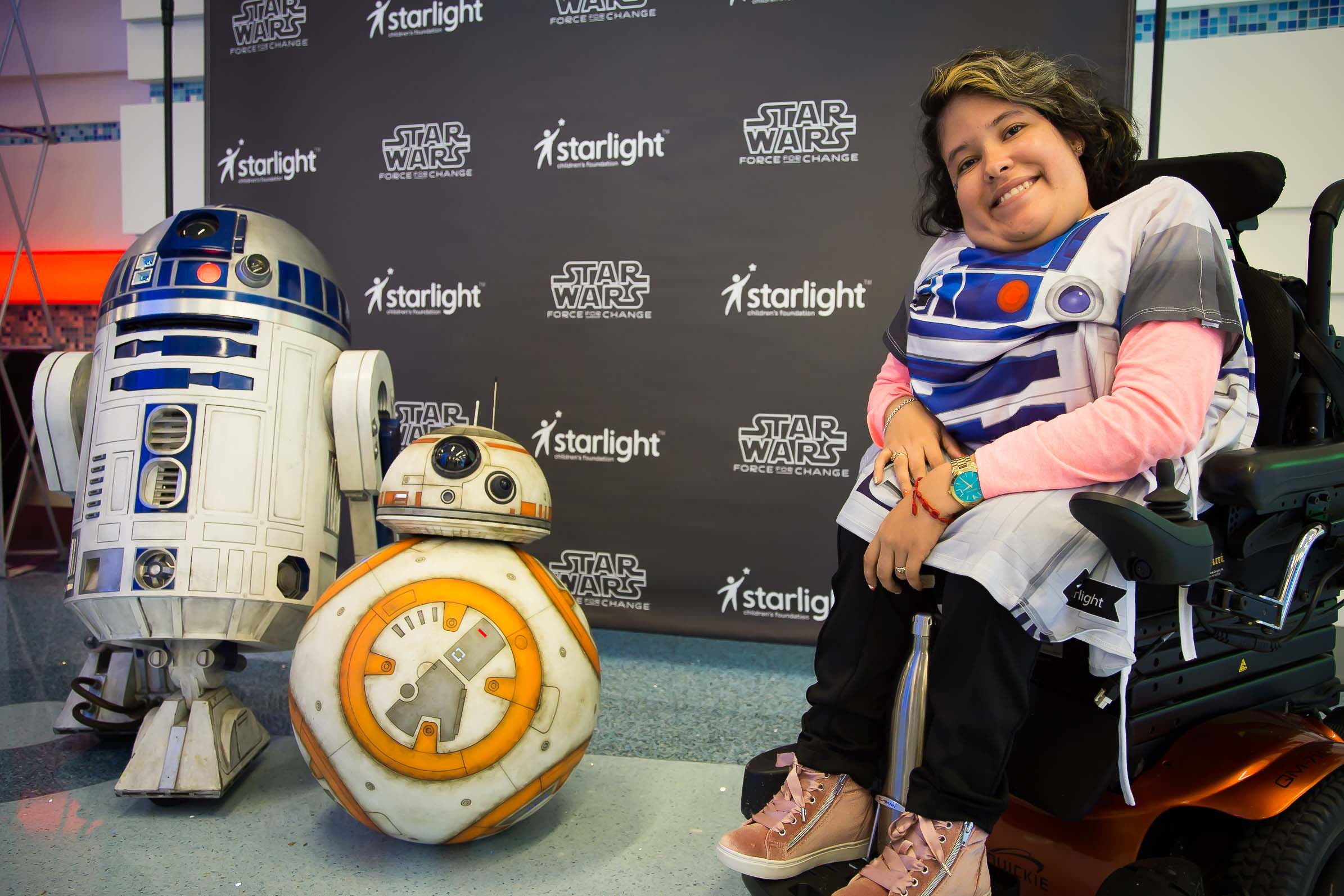 A child posing in their R2-D2 themed gown, alongside BB-8 and R2-D2