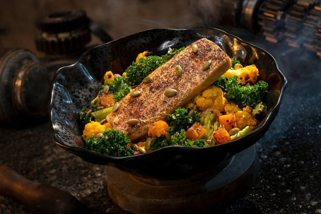 The Oven-roasted Burra Fish, found at Docking Bay 7 Food and Cargo inside Star Wars: Galaxy's Edge, features Dijon-crusted sustainable fish with mixed greens, roasted vegetables, quinoa and pumpkin seeds with a creamy green curry ranch dressing. (David Roark/Disney Parks)