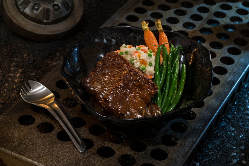 "The Ithorian Garden Loaf, found at Docking Bay 7 Food and Cargo inside Star Wars: Galaxy's Edge, is a plant-based ""meatloaf"" dish served with roasted vegetable mash, seasonal vegetables and mushroom sauce. (David Roark/Disney Parks)"