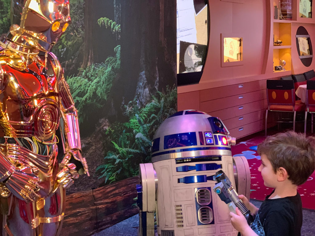 A young fan meets C-3PO and R2-D2 on Star Wars Day at Sea.