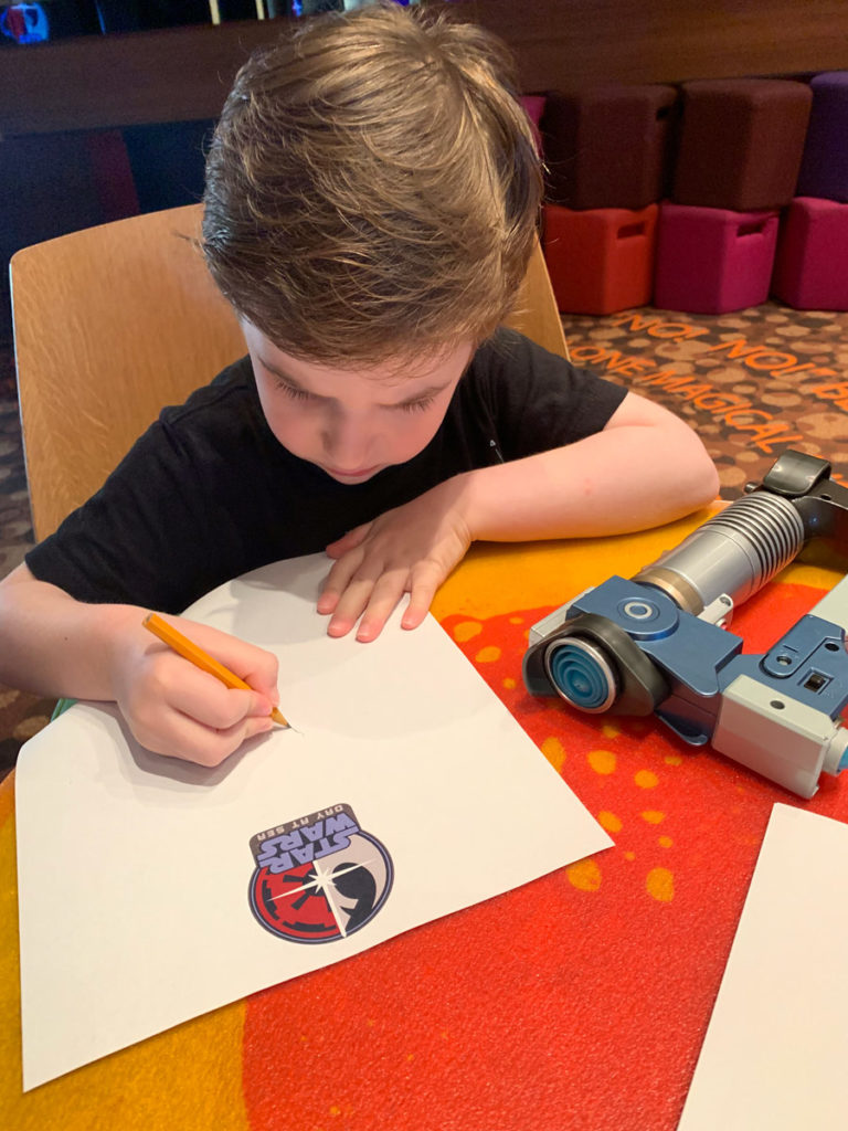 A young fan draws porgs during Star Wars Day at Sea on the Disney Fantasy.