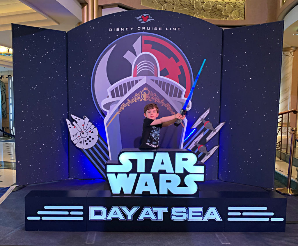 A young fan with his lightsaber on Star Wars Day at Sea.