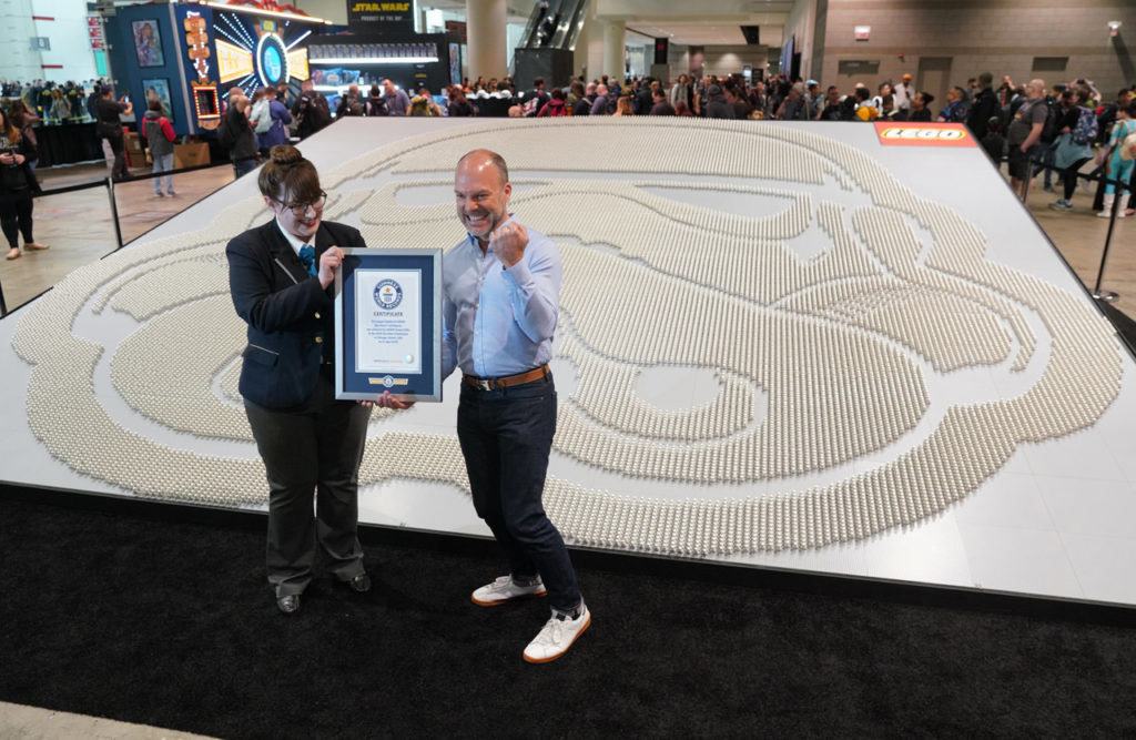 Michael McNally, LEGO Group senior director of brand relations, right, accepts a certificate of achievement from Guinness World Records.