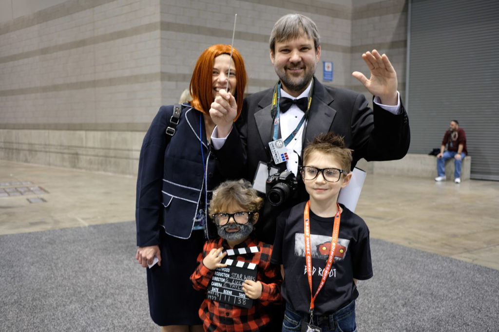 Family of cosplayers dressed as Kathleen Kennedy, George Lucas, J.J. Abrams, and John Williams.