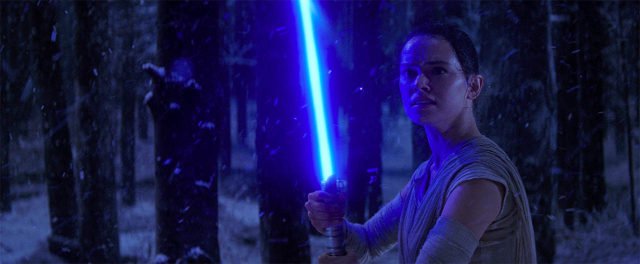 Rey takes a lightsaber from Kylo Ren.