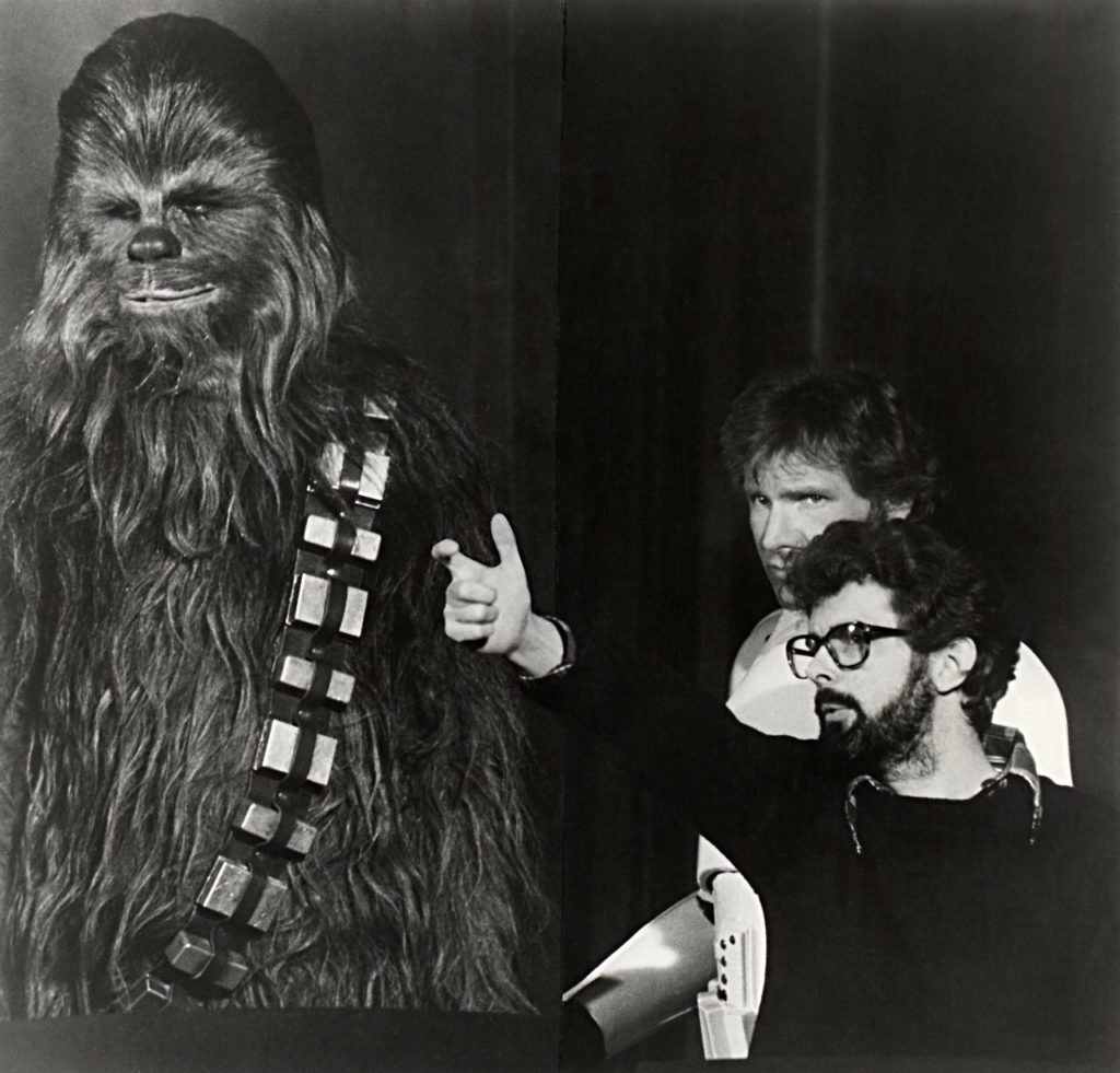 Peter Mayhew, in full costume as Chewbacca, taking direction from George Lucas alongside Harrison Ford
