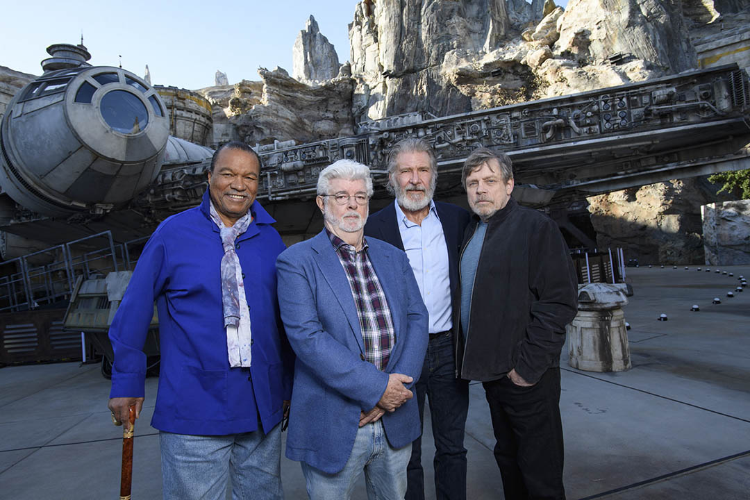 Actor Billy Dee Williams, Star Wars creator George Lucas, and actors Harrison Ford and Mark Hamill pose in front of the Millennium Falcon at Star Wars: Galaxy's Edge at Disneyland Park on May 29, 2019.