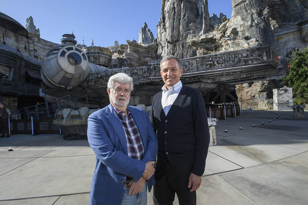 Bob Iger, Walt Disney Company Chairman and CEO (right), and George Lucas, Star Wars creator, stand in front of the Millennium Falcon at Star Wars: Galaxy's Edge at Disneyland Park on May 29, 2019.