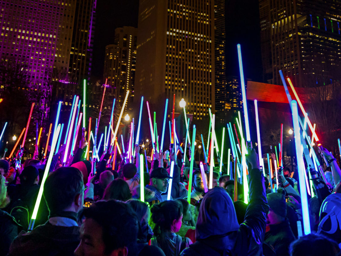 Star Wars fans hold lightsabers at night in Chicago.
