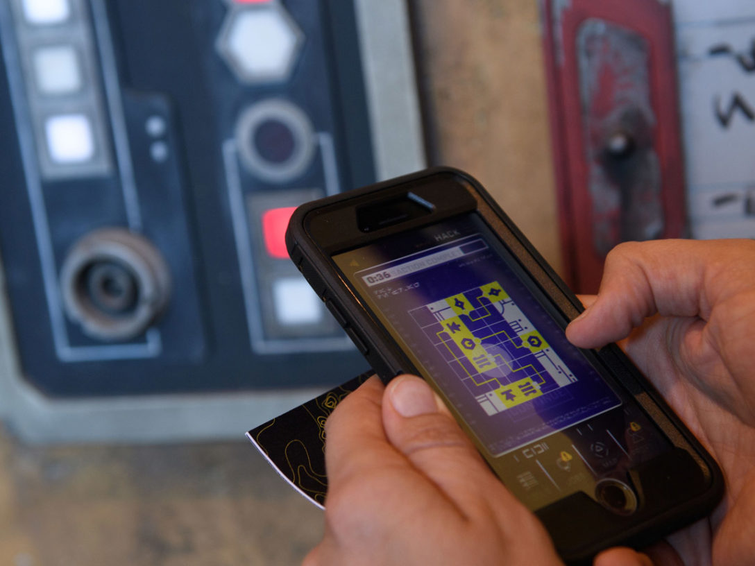 A visitor uses the Disney Play app shown inside Star Wars: Galaxy's Edge.