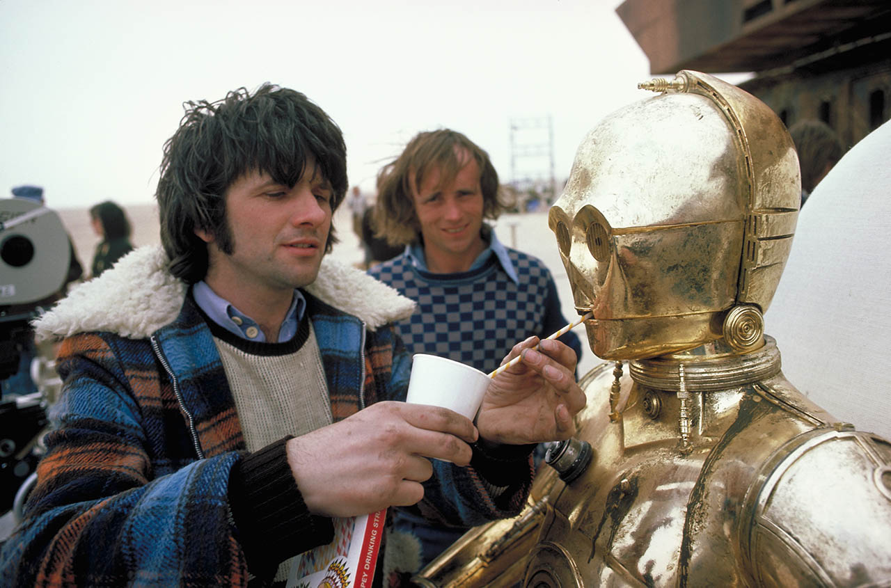 Anthony Daniels as C-3PO is helped with a drink on the set of Tatooine.