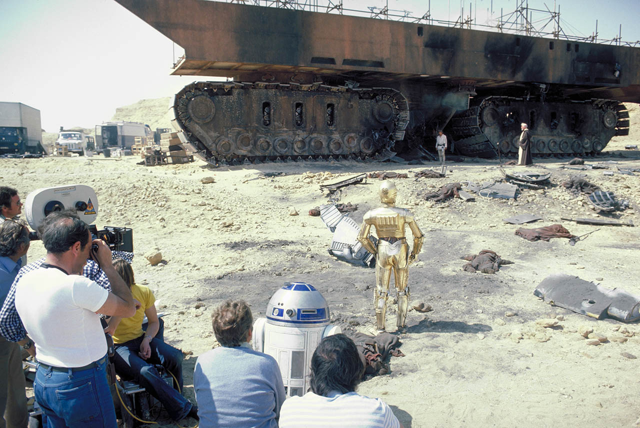 """R2-D2, C-3PO, Luke Skywalker (Mark Hamill), and Obi-Wan Kenobi (Alec Guinness) survey the destruction of Jawas and their sandcrawler on Tatooine."""