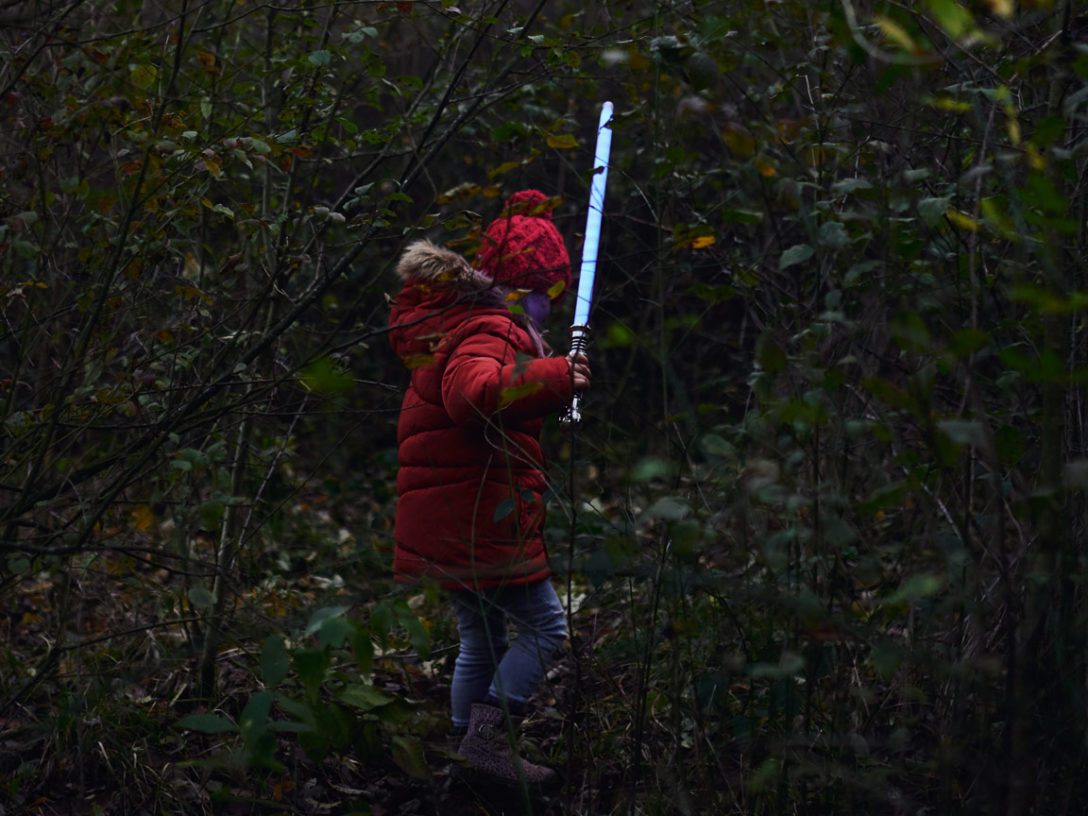 Girl plays in the woods with a lightsaber from the Star Wars Families project