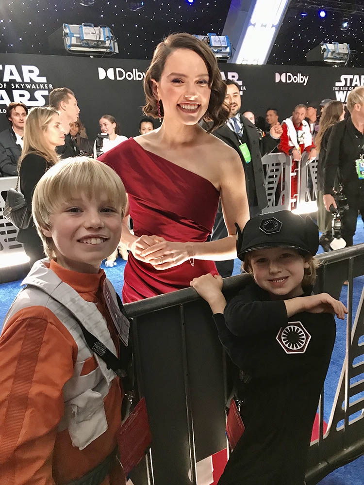 Daisy Ridley poses with two young fans.