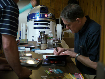 R2-D2 watches Ryder Windham signing books for blood donors in Attleboro, Massachusetts.
